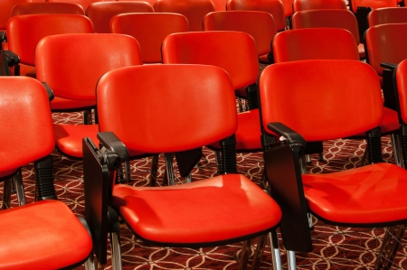 red recliners stand rows in an empty conference hall photo