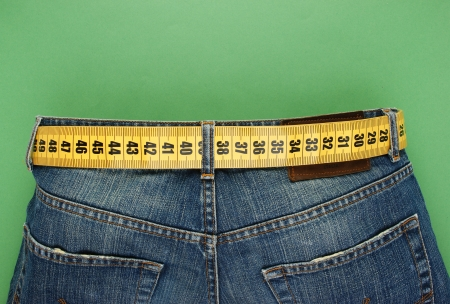 weight loss plan: jeans con cintura metro dimagrante su sfondo verde Archivio Fotografico