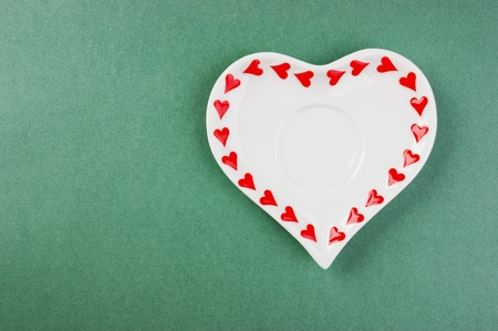 Heart form white plate on a green background photo