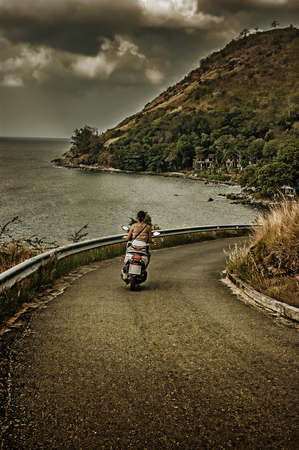 girl riding a motorcycle on a country road photo