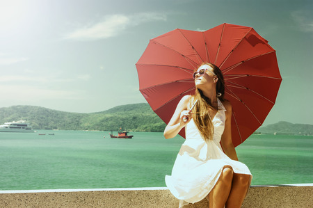 parapet: young girl with a red umbrella sits on the waterfront and looks at the sea