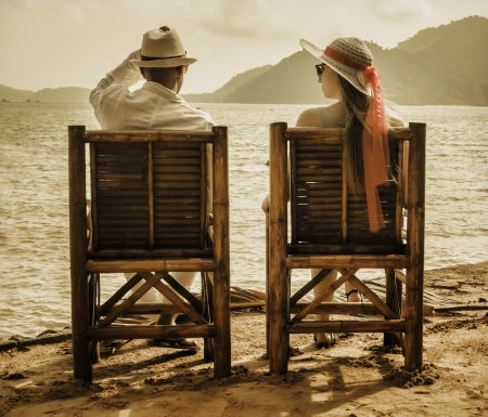 young man and girl sitting on the beach photo