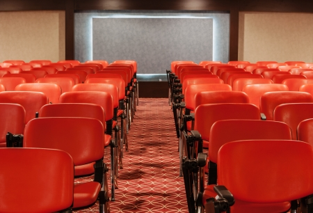 red recliners stand rows in empty conference hall photo