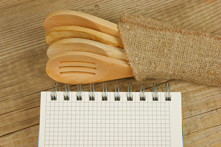 wooden spoon and notebook on old wooden table photo