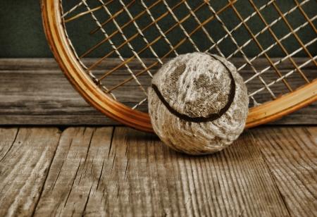 나무 바닥에 오래 된 테니스 공 및 라켓