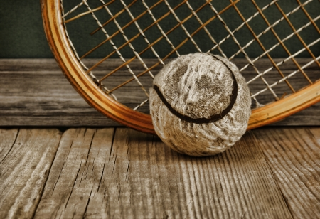 old tennis ball and racket on a wooden floor photo
