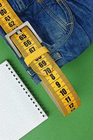jeans with meter belt slimming and notebook on the green  photo