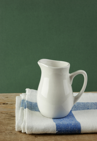 dishcloth: White jug and dishcloth on old wooden table over green  Stock Photo