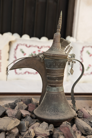 Old Arabic metal pitcher on hot coals photo