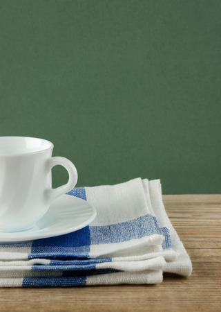 dishcloth: White coffee cup and dishcloth on old wooden table over green background