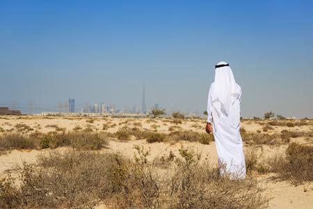 hombre arabe: Hombre árabe en traje nacional se sitúa en el desierto y se ve en la ciudad de Dubai Foto de archivo