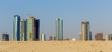 industrialized: Sandy Desert and modern city in Sharjah. It is the most industrialized emirate in UAE.
