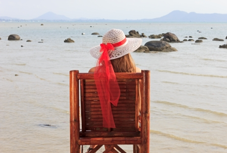a young girl sitting on a chair and looks at the sea photo