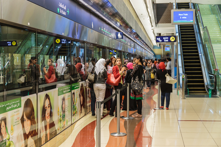 females only: DUBAI, UAE - NOVEMBER 3, 2013: Interior of metro station in Dubai. The train has a special wagon for females only Editorial