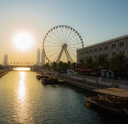 third wheel: SHARJAH, UAE - OCTOBER 28: Ferris wheel in Al Qasba. Sharjah - third largest and most populous city in United Arab Emirates, on October 28, 2013.