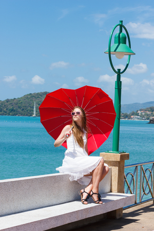 young girl with a red umbrella sits on the waterfront  photo