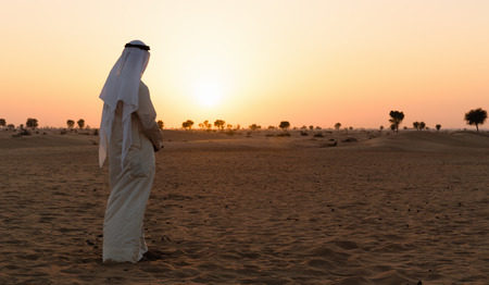 Arab man stands alone in the desert and watching the sunset  photo