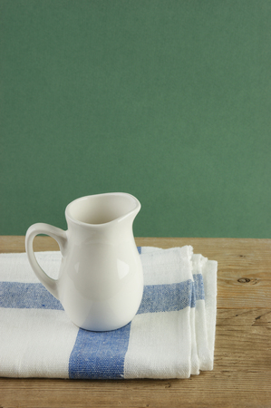 dishcloth: White jug and dishcloth on old wooden table over green background