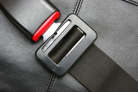 cinturon de seguridad: cinturón de seguridad en una silla de cuero negro Foto de archivo