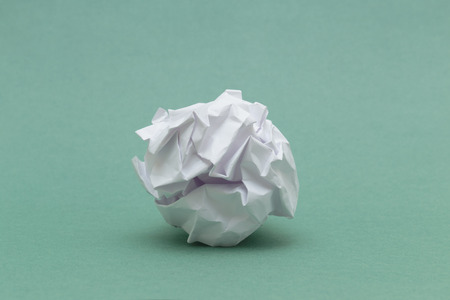 wad of crumpled paper on green background