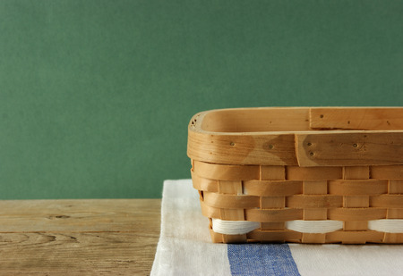 dishcloth: empty wicker basket on an old wooden table against grunge wall