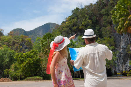 woman and man looking at the map on a tropical landscape photo