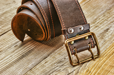 leather belt: leather belt with a buckle on a wooden board