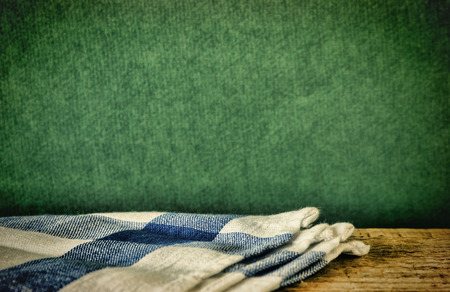 dishcloth: Table-napkin and old wooden deck table with green grunge background