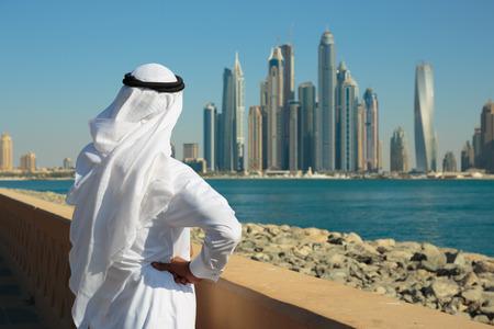 DUBAI, Verenigde Arabische Emiraten - 7 november: Moderne gebouwen in Dubai Marina ,, VAE. In de stad van kunstmatige kanaal lengte van 3 kilometer langs de Perzische Golf. Man in Arabische jurk ziet er op de stad