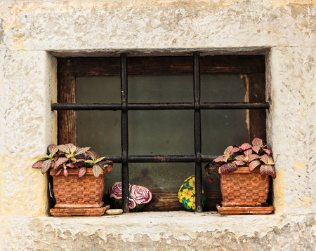 Window in an old house decorated with flower pots and flowers photo