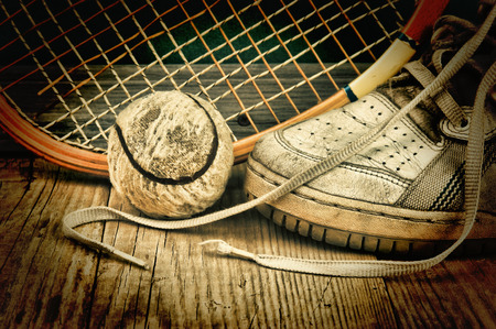 oude tennisbal en racket met sneakers op een houten vloer Stockfoto
