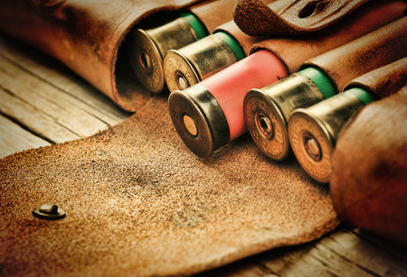 cazador: Cartuchos viejos de la caza y la bandolera sobre una mesa de madera