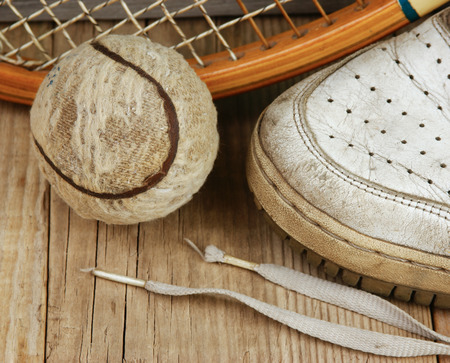 old tennis ball and racket with sneakers on a wooden floor photo