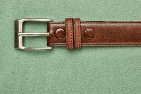 leather belt with a buckle on a green background photo
