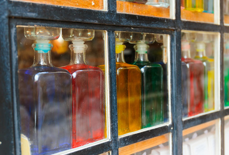 distillate: Bottles with colored liquid on the window behind the glass
