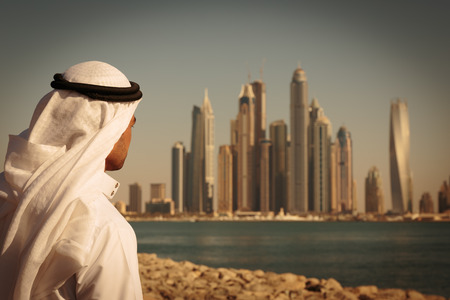 arabic: DUBAI, UAE - NOVEMBER 7: Modern buildings in Dubai Marina,, UAE. In the city of artificial channel length of 3 kilometers along the Persian Gulf. Man in Arab dress looks at the city. Toned