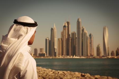 DUBAI, Verenigde Arabische Emiraten - 7 november: Moderne gebouwen in Dubai Marina ,, VAE. In de stad van kunstmatige kanaal lengte van 3 kilometer langs de Perzische Golf. Mens in Arabische kleding kijkt naar de stad. afgezwakt
