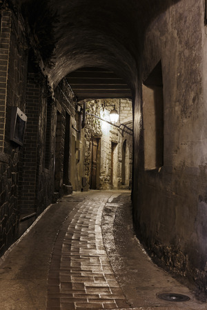 cobbled: Narrow cobbled street in old town Peille at night, France.