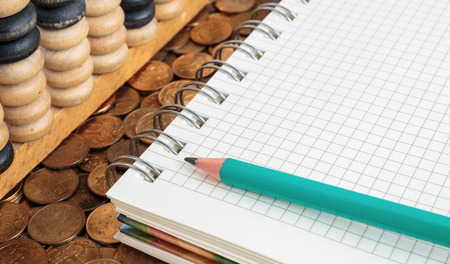 Notepad with pencil and abacus on a pile of coins photo
