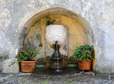 small fountain in a stone niche photo
