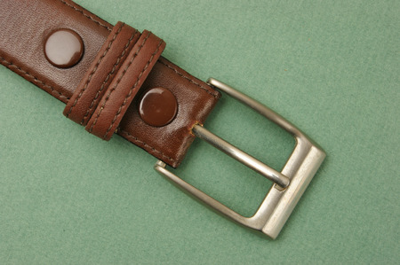 waistband: leather belt with a buckle on a green background