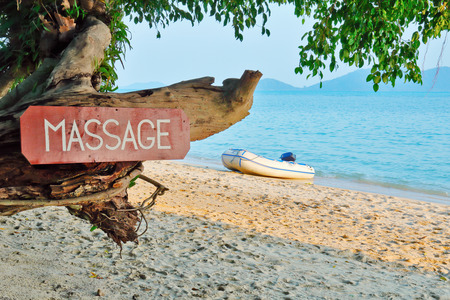 Old signboard with the inscription, massage, on a tropical beach Foto de archivo