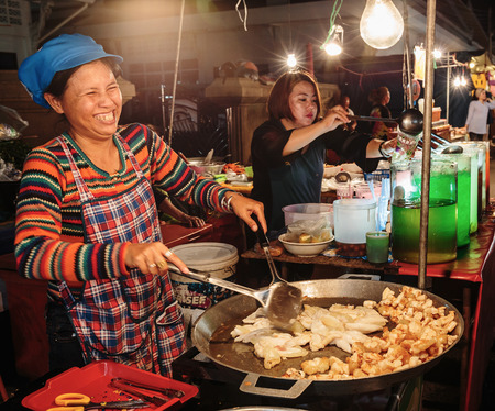 night market: PATTAYA, THAILAND - APRIL 4, 2015: Woman in a street cafe  fry food and smiling