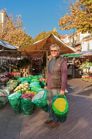 flower seller: NICE, FRANCE - OCTOBER 30, 2014: Smiling seller florist in flower shop
