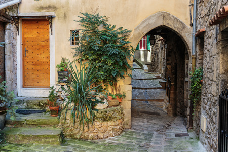 cobbled: Narrow cobbled streets with flowers in the old village Lyuseram, France Stock Photo