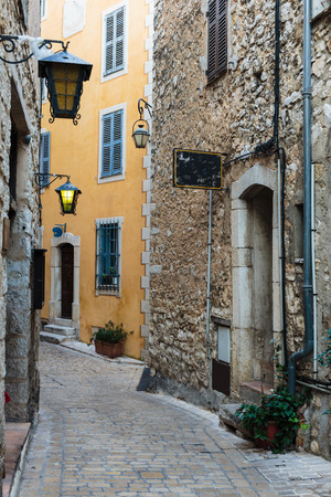 cobbled: Narrow cobbled street with flowers in the old village Tourrettes-sur-Loup , France. Stock Photo