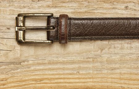 buckle: leather belt with a buckle on a wooden board