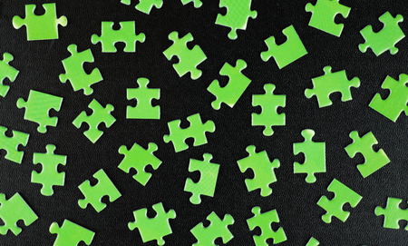 Green puzzles on a black leather background