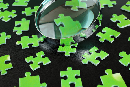 Green puzzles and magnifying glass on a black leather background