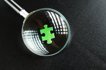 poser: Green puzzles and magnifying glass on a black leather background